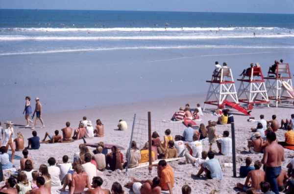 An old photograph looking out to the ocean with a large group of people on the beach.