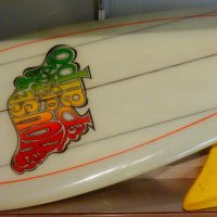 """white paipo with a red, yellow and green """"House of Paipo"""" logo on it"""